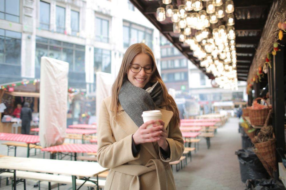 Ragazza in una città con un caffè da asporto in mano, foto di Andrea Piacquadio da Pexels