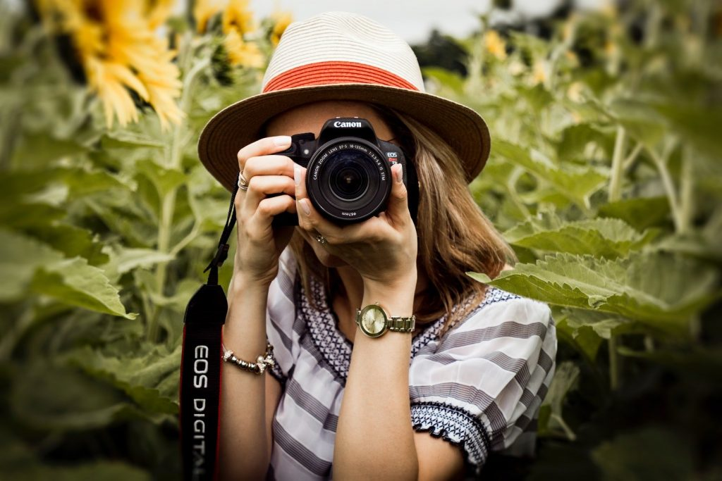 Ragazza che scatta una fotografia in un campo, immagine di Andre Furtado da Pexels